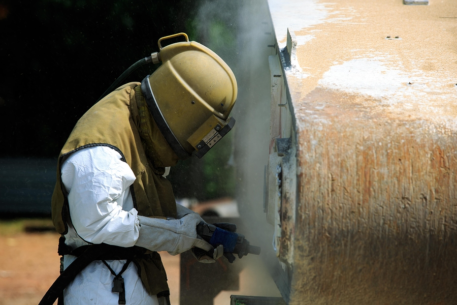 Worker is removing paint by air pressure sand blasting